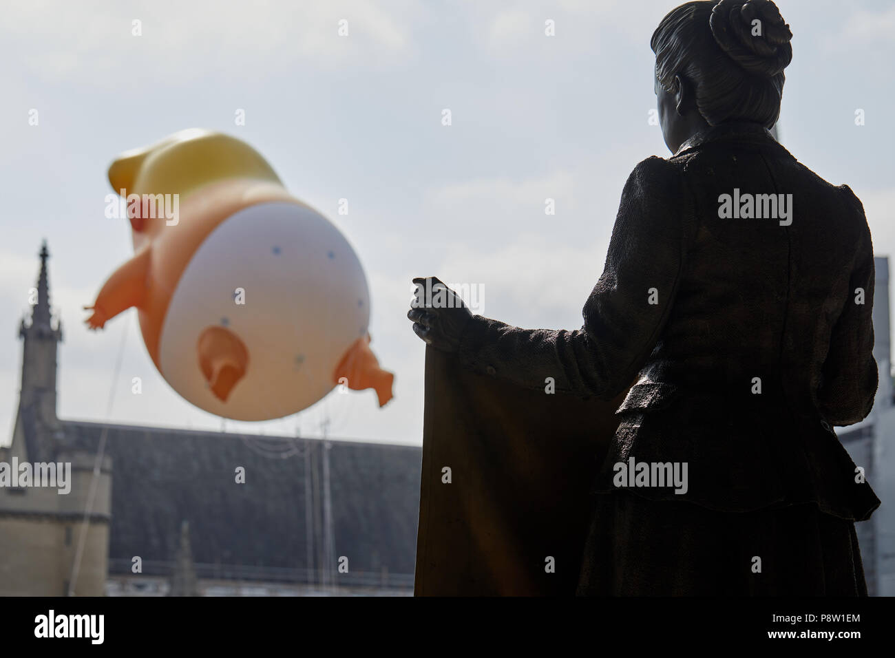 London, U.K. - 13 July 2018: The statue of suffragist Millicent Fawcett looks out at a balloon mocking Donald Trump in Parliament Square, London. - Stock Image