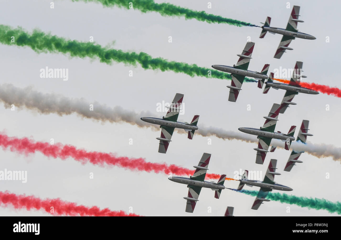 Fairford, UK, 13 July 2018. Four planes of the Italian Air Force aerobatic team, the  Frecce Tricolori, on the first day of the 2018 Royal International Air Tattoo in Fairford, England. They are flying under coloured smoke produced by other members of the team and producing their own smoke (picture taken 13 July 2018) Credit: Ceri Breeze/Alamy Live NewsCredit: Ceri Breeze/Alamy Live News  - Stock Image
