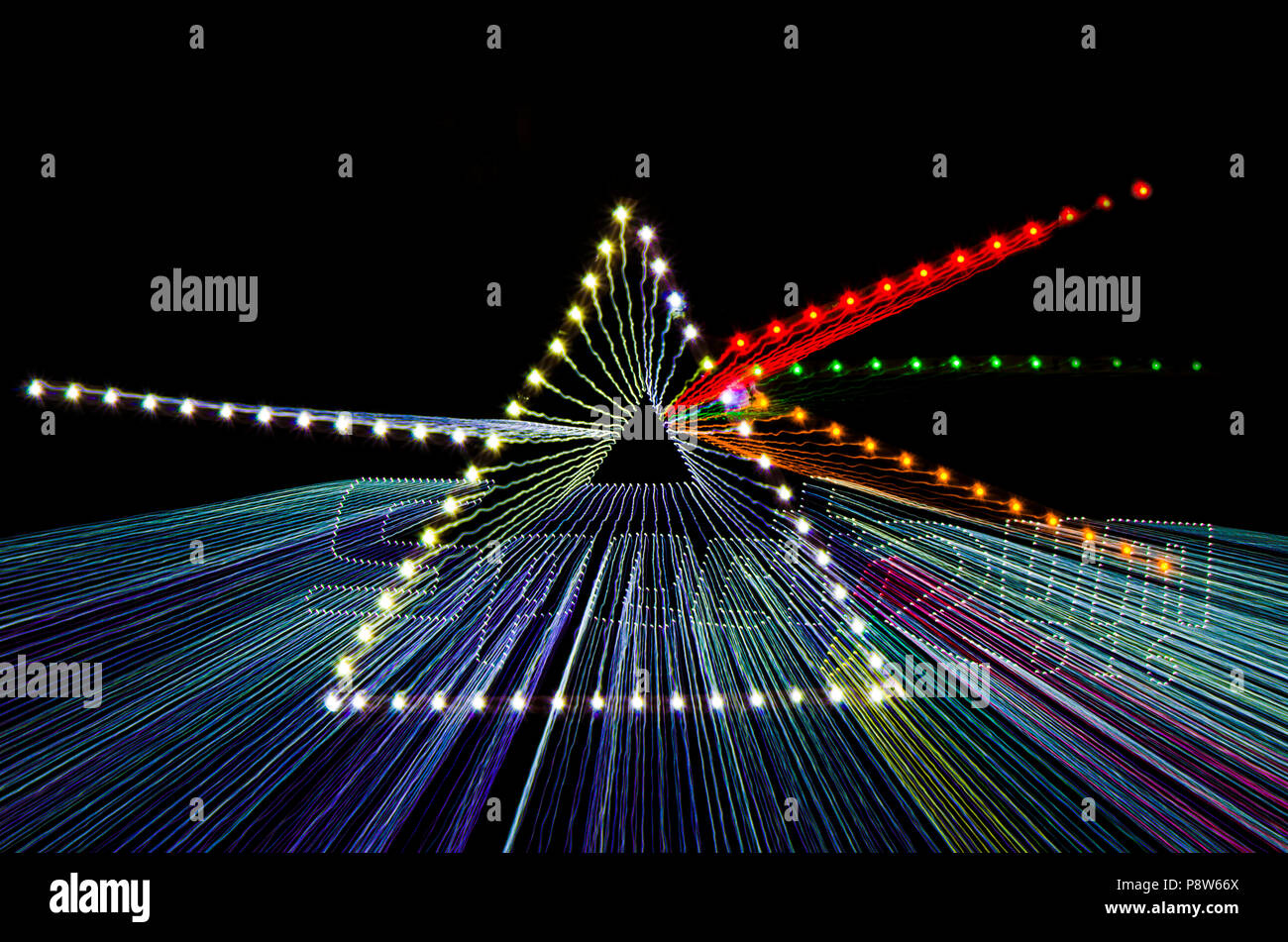 Zoom burst, illusive image of the concept of white light dispersion through a prism showcased using different colour LED bulbs over black background. - Stock Image