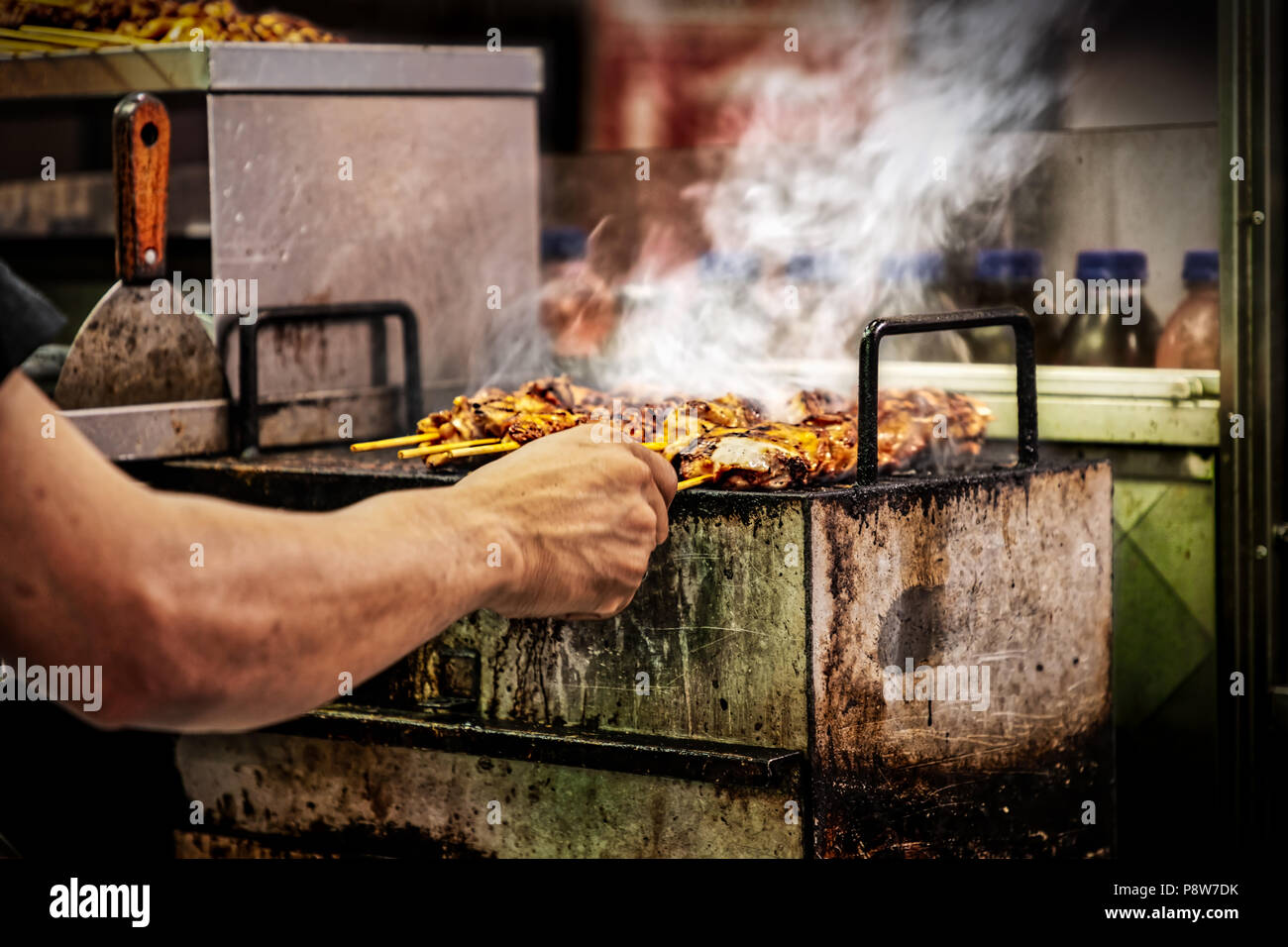A cook at a food stand in New York City with kebabs on skewers. - Stock Image