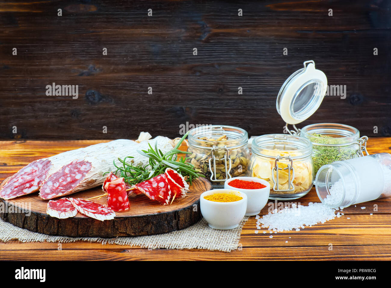 Sliced cured sausage with spices and a sprig of rosemary on dark wooden rustic background. - Stock Image
