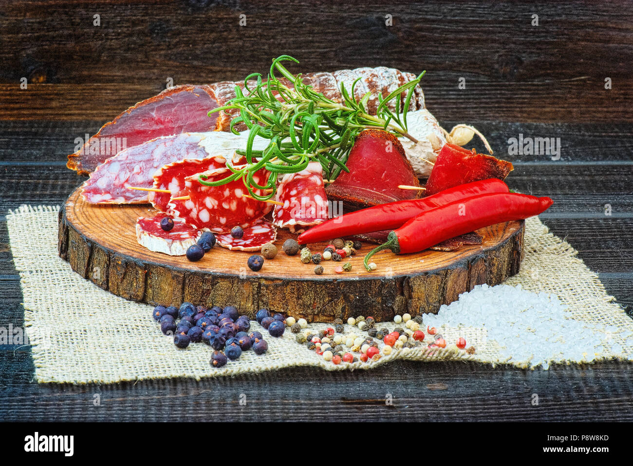 Sliced cured sausage and bresaola with spices and a sprig of rosemary on dark wooden rustic background. - Stock Image
