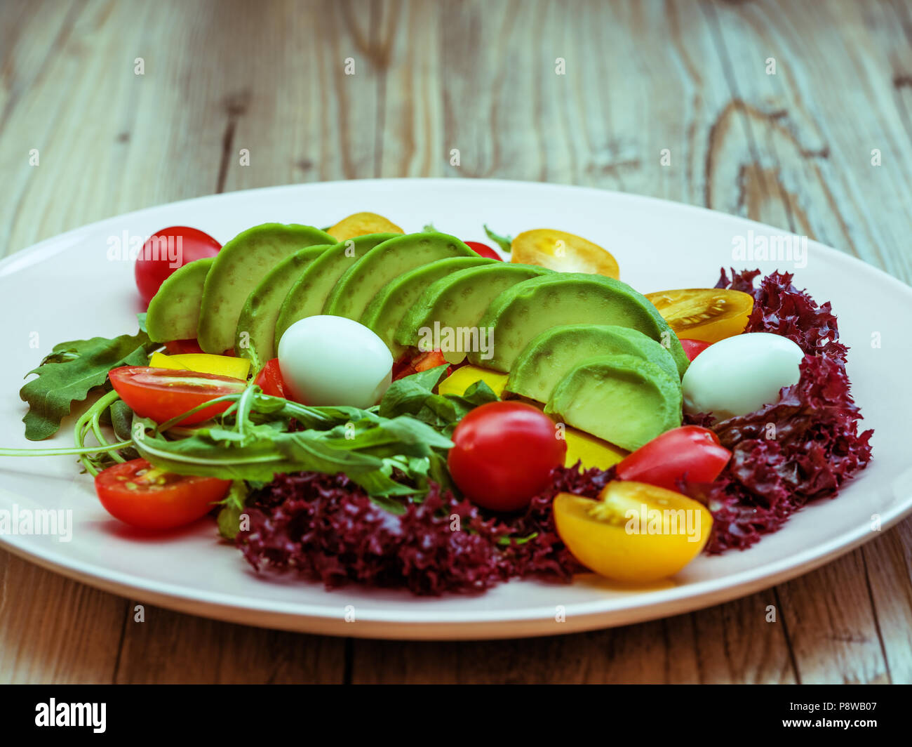 Dietary avocado salad with cherry tomatoes, quail eggs, yellow and red pepper and lettuce. Avocado is source of nutrition, vitamins. Studio shot. - Stock Image