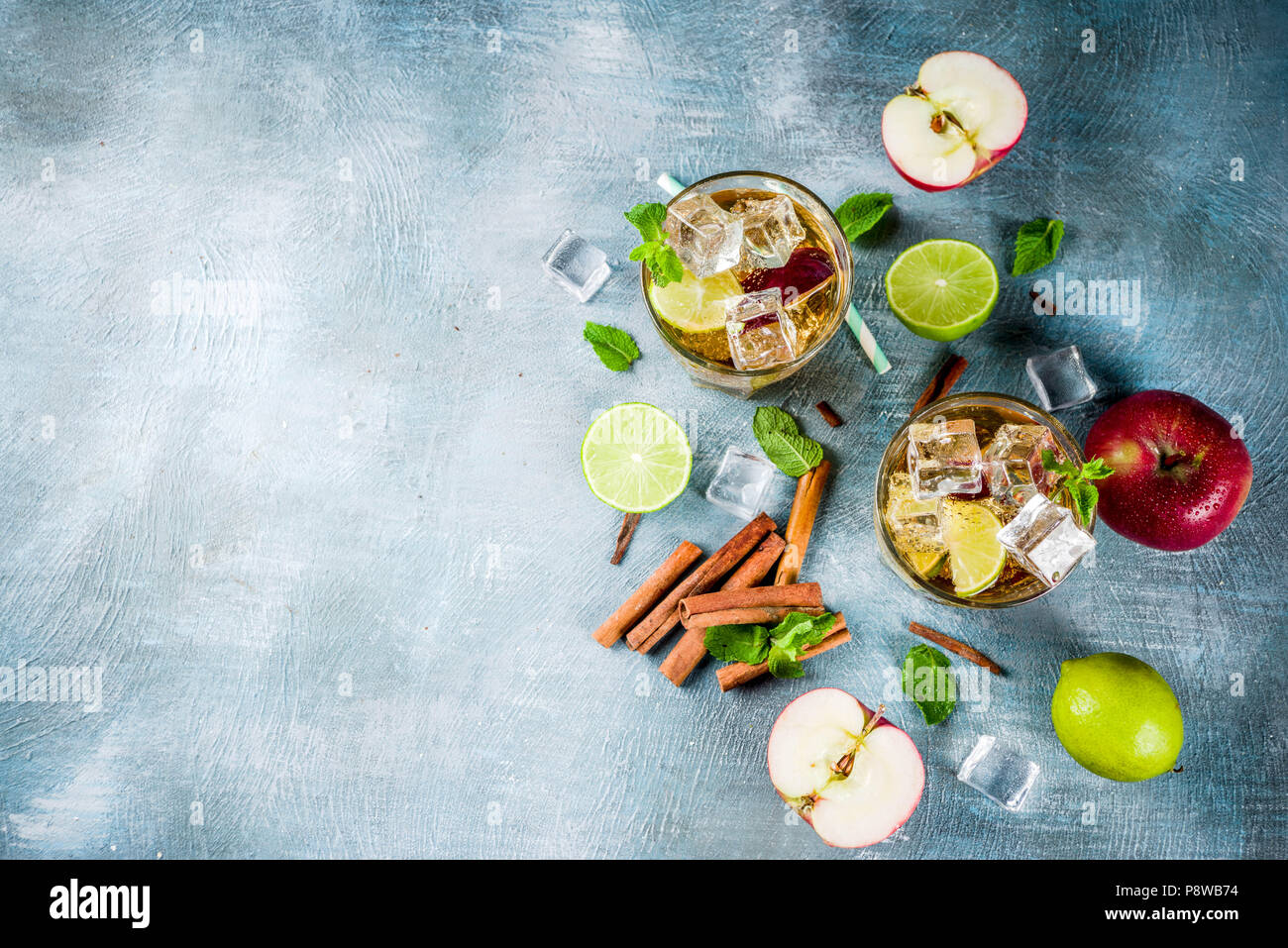 Spicy cinnamon apple iced tea or lemonade cocktail, summer refreshment drink, blue background copy space - Stock Image