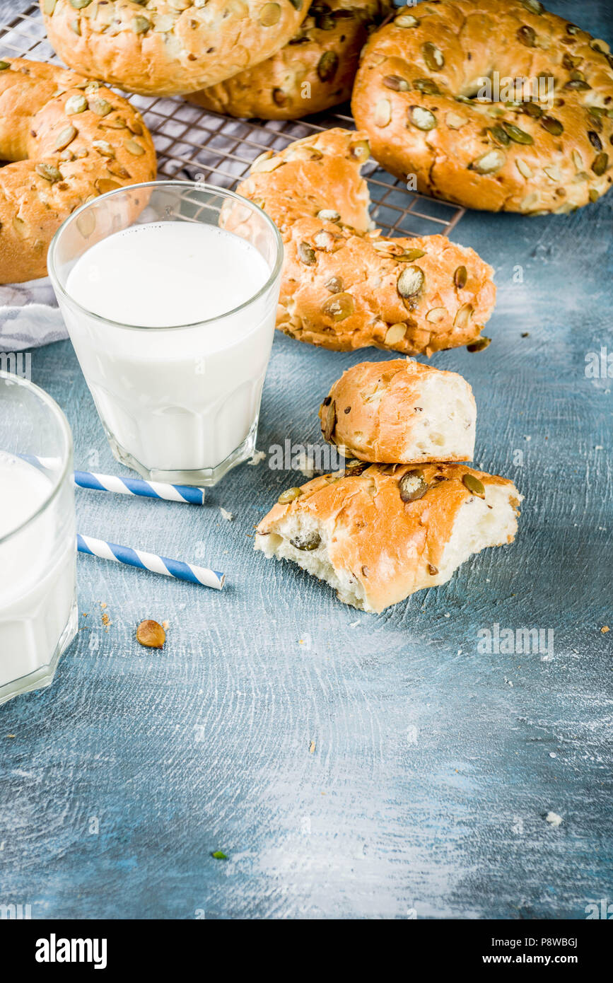 Healthy breakfast concept, home made cereal bagels with milk glass, on blue background copy space - Stock Image