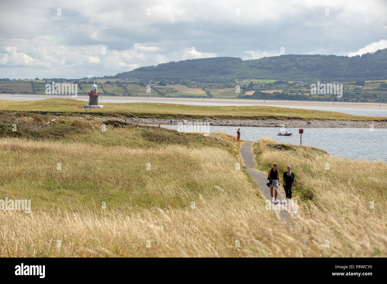 Tourists walking along the Rosses Point Coastal Way trail with Oyster Island and its famous lighthouse in the background on a sunny summer day. - Stock Image