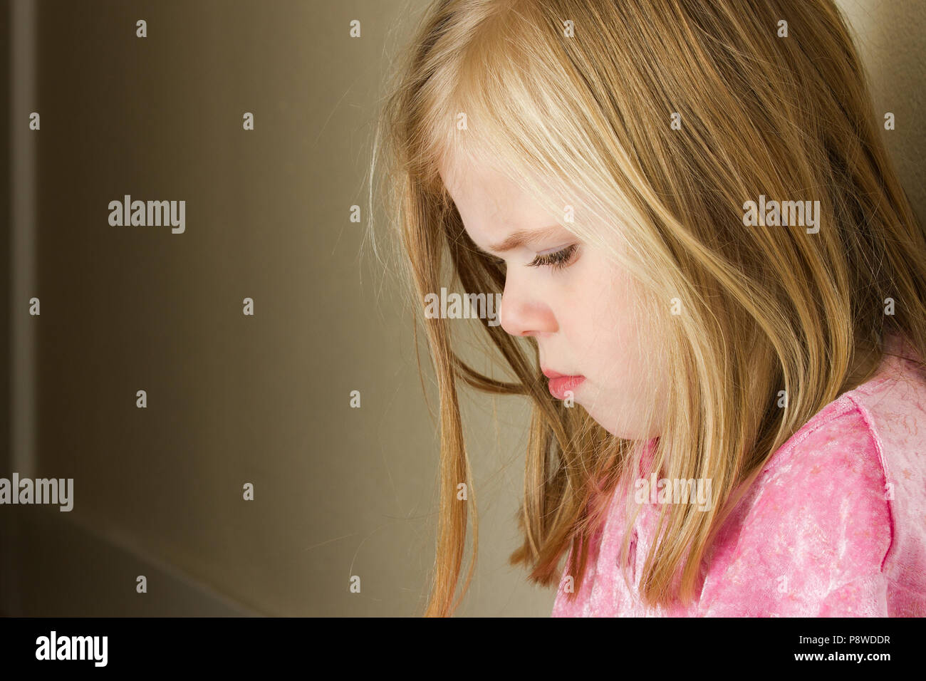 Child could be sad due to abuse, domestic violence, or even sad due to a bully - Stock Image