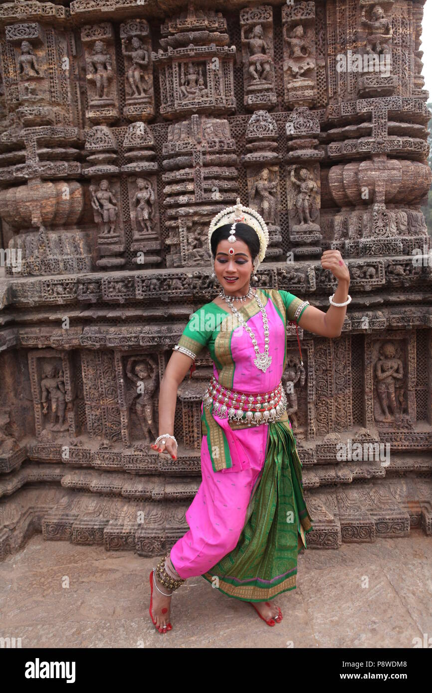 odissi is one of the eight classical dance forms of india,from the state of odisha.here the dancer poses before temples with sculptures - Stock Image