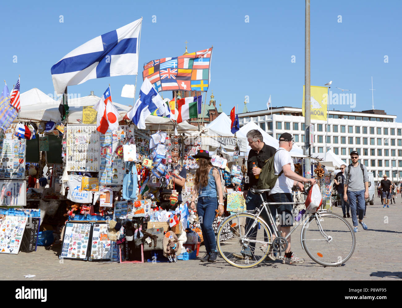 HELSINKI, FINLAND - May 14, 2018: Tourists peruse a stall laden with souvenirs and flags in Market Square, Helsinki - Stock Image