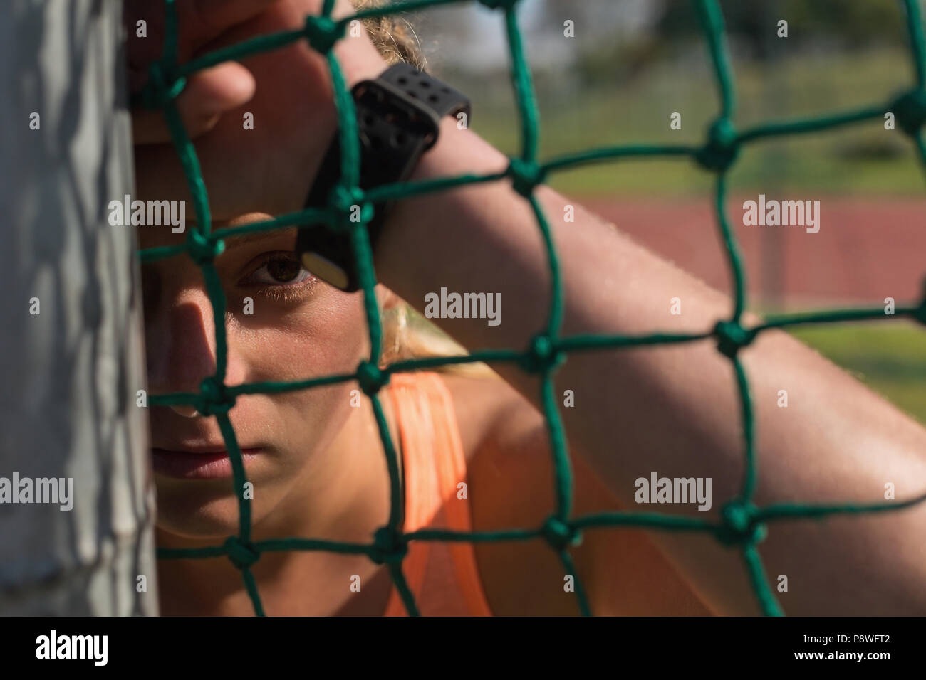Female athlete relaxing at sports venue - Stock Image