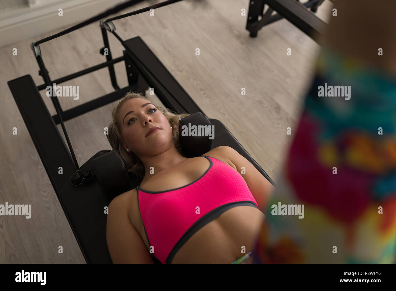 Woman exercising on stretching machine - Stock Image