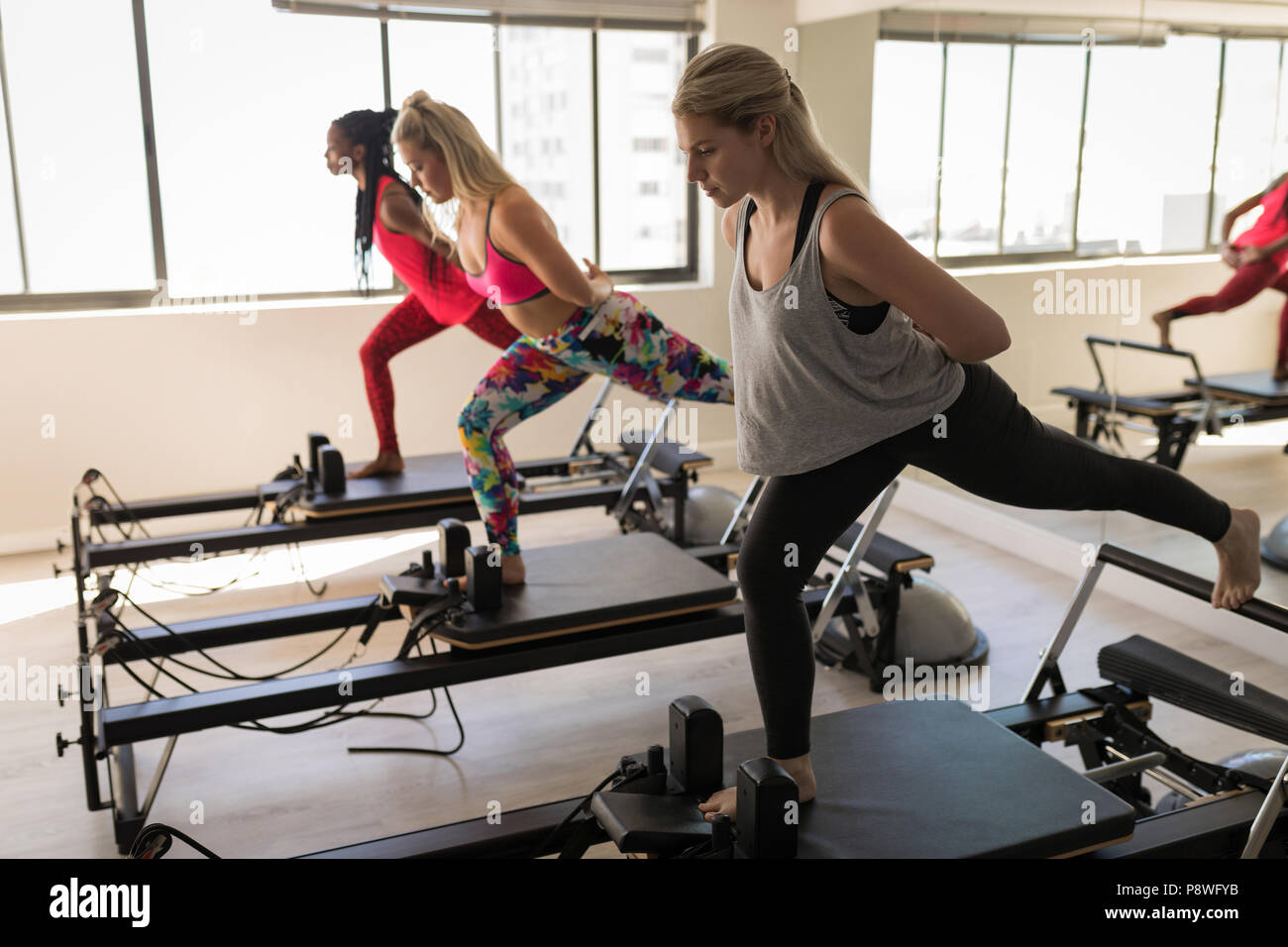 Group of women exercising on stretching machine - Stock Image