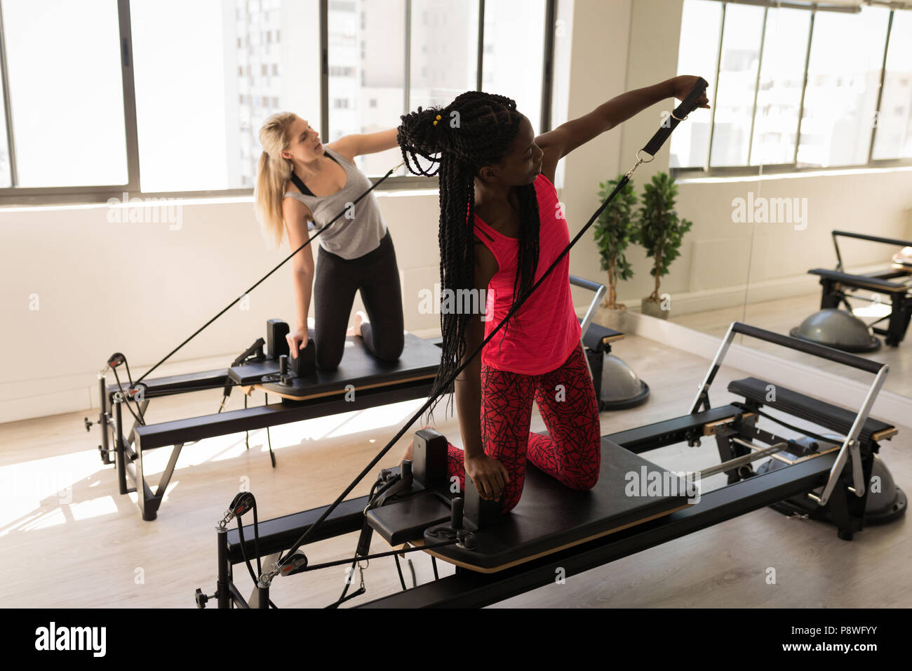 Two women exercising on stretching machine - Stock Image