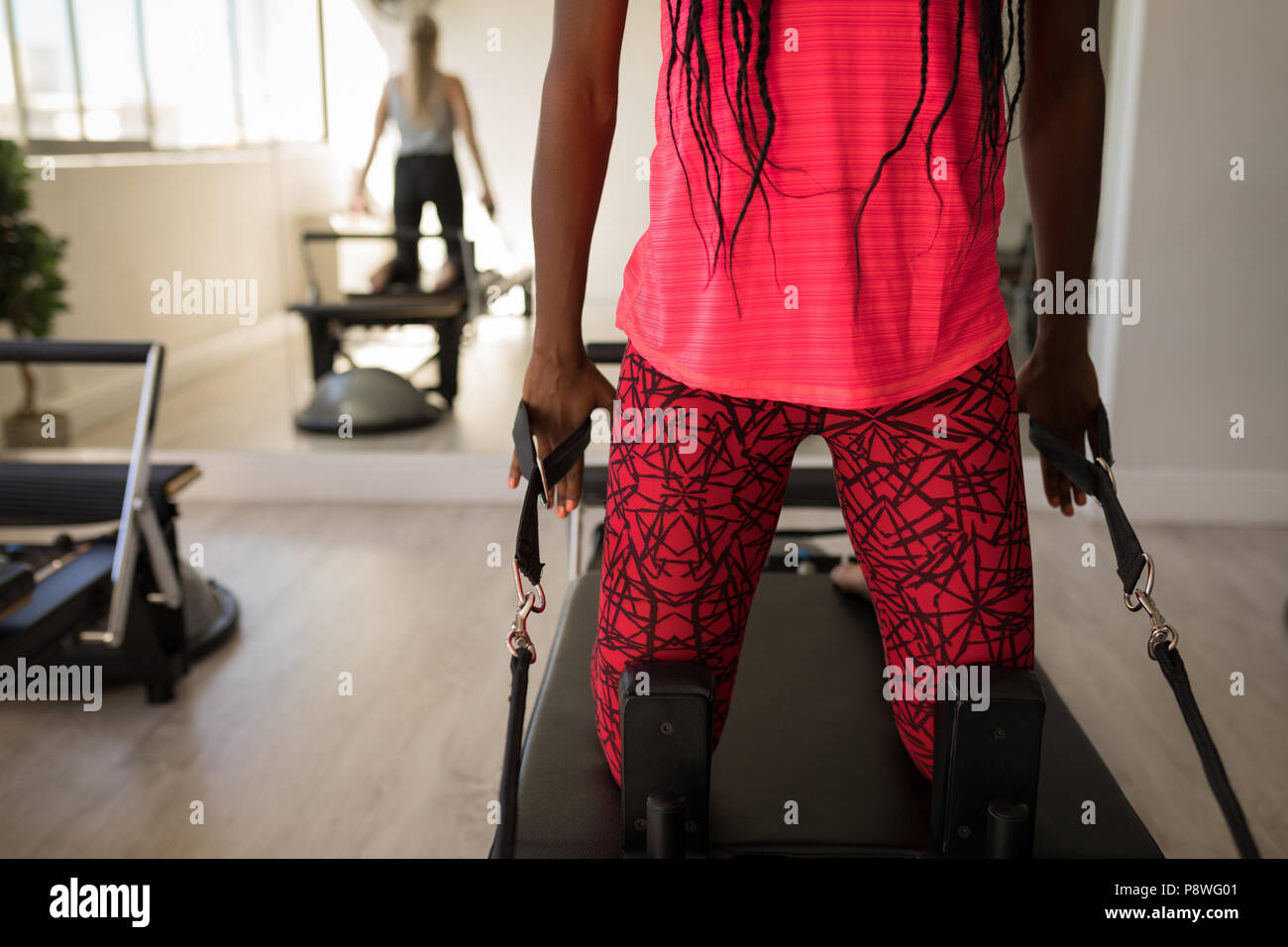 Woman exercising on stretching machine in fitness studio - Stock Image