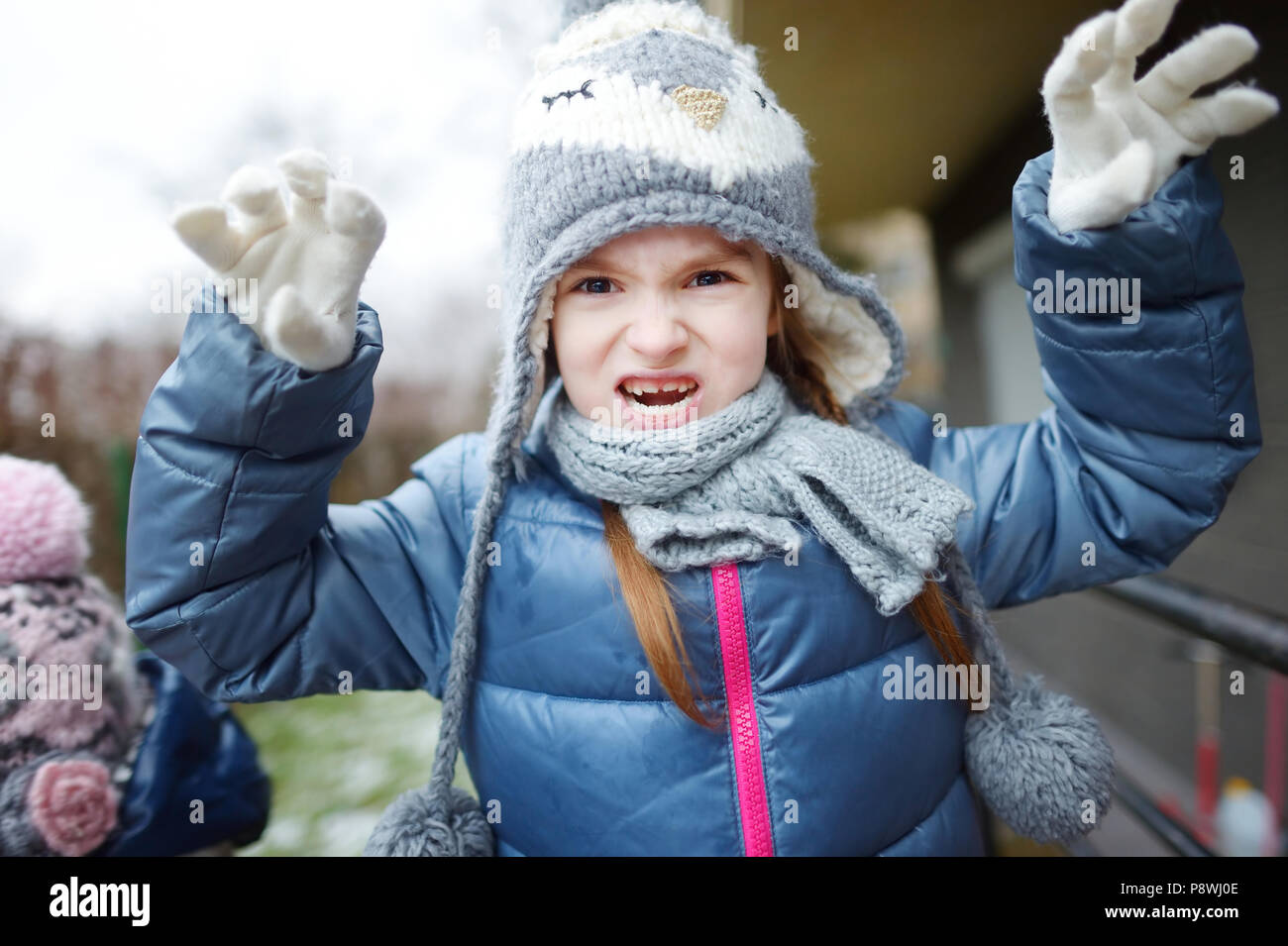 adorable little girl wearing winter hat making funny faces on