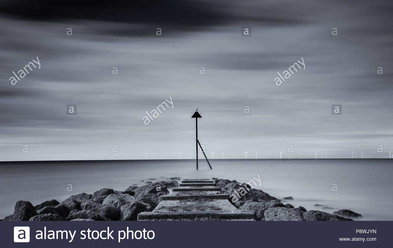 Moody photograph of groyne marker, Colwyn Bay, Wales - Stock Image
