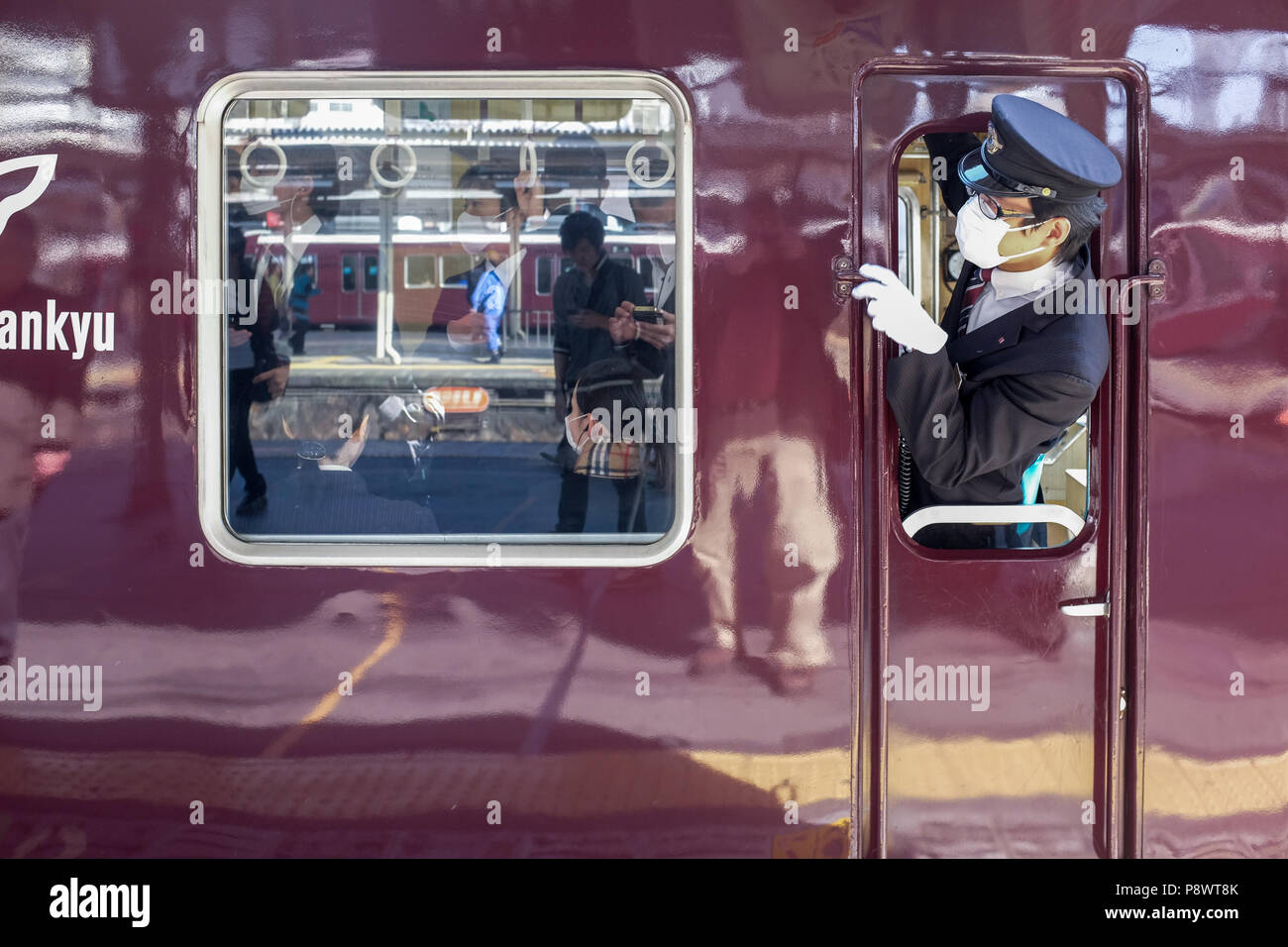 Engine driver on a train for Hankyu Railway Kobe line. This is one of three major commuter rail lines in the Kobe Osaka area. - Stock Image