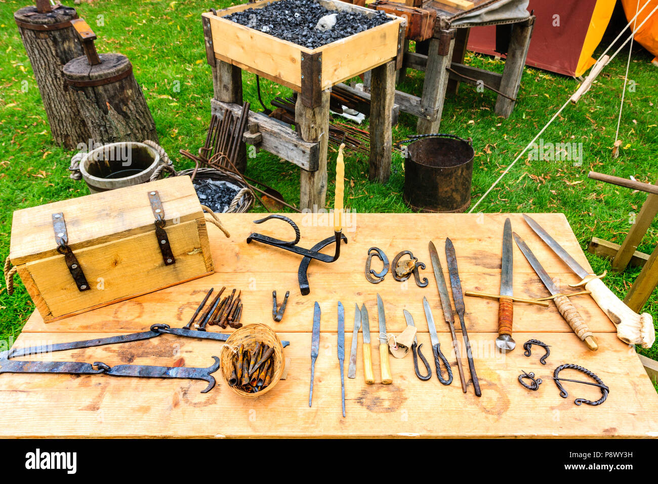 Re-enactment, living history. Display on table of various tools that are made by medieval blacksmith, knifes, tools and daggers. - Stock Image