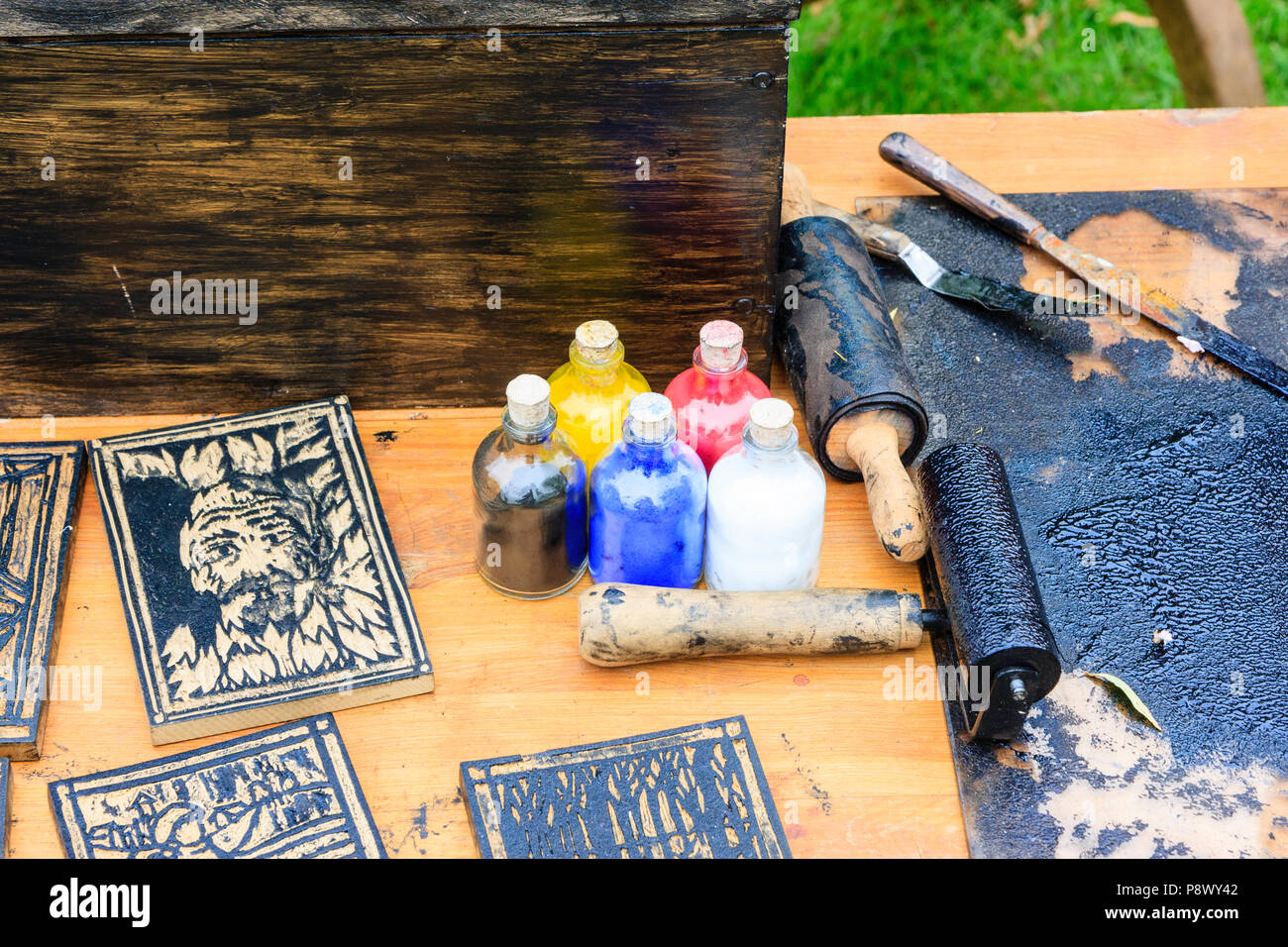 Re-enactment, living history. Medieval re construction of printing, woodblock prints and bottles of coloured inks on table. - Stock Image
