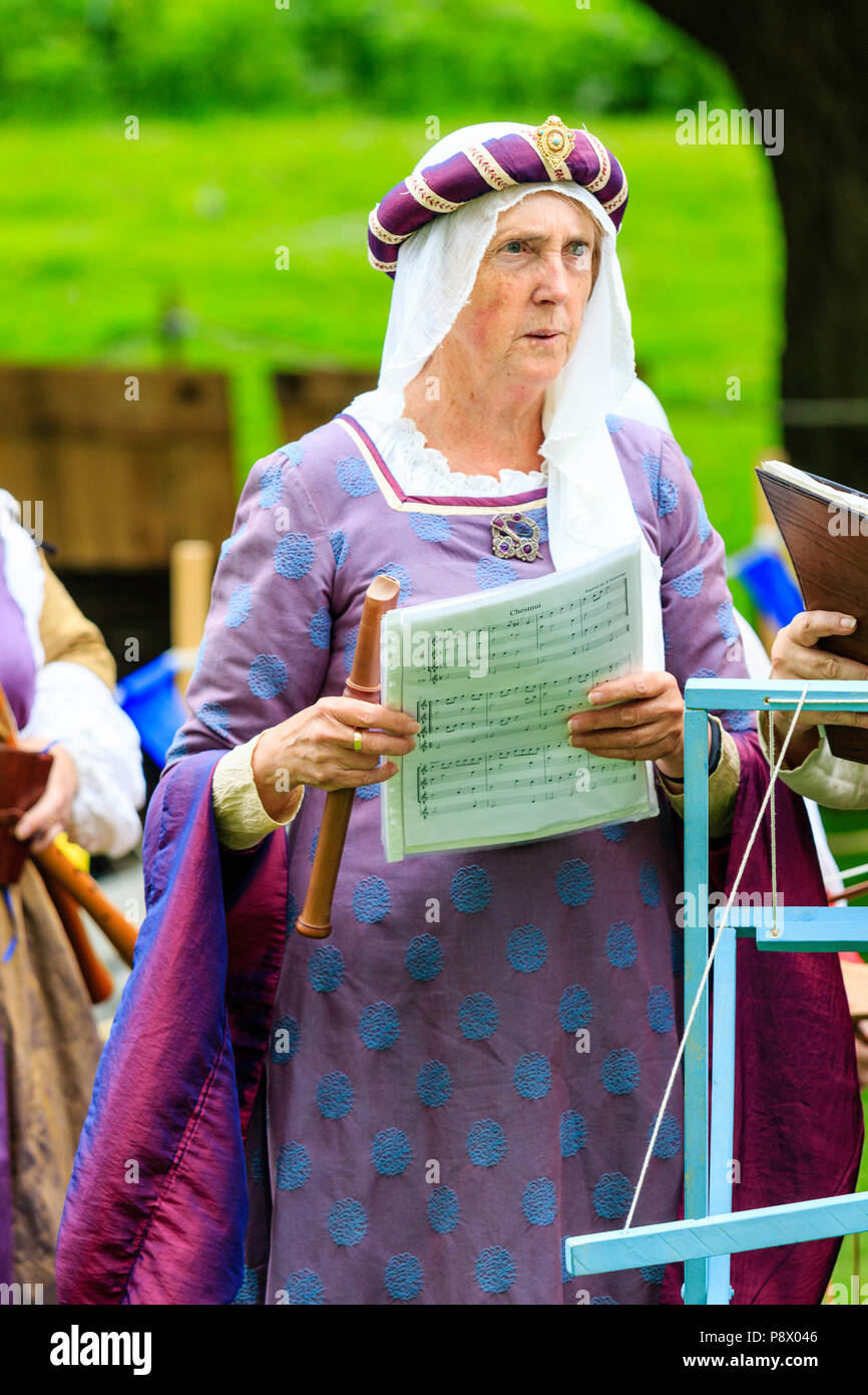 Medieval Living history reenactment. Mature woman, 50s, dressed in medieval minstrel costume, holding sheet music to 'chestnut' tune and holding flute - Stock Image
