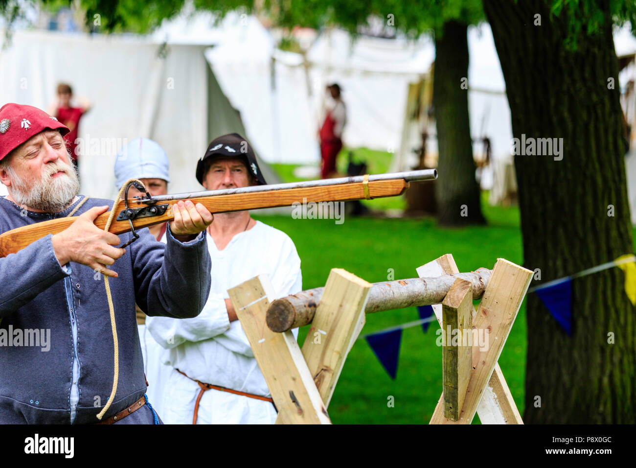 Man in medieval costume, about to fire harquebus, arquebus, early reconstructed gun, circa 16th century at living history reenactment event - Stock Image