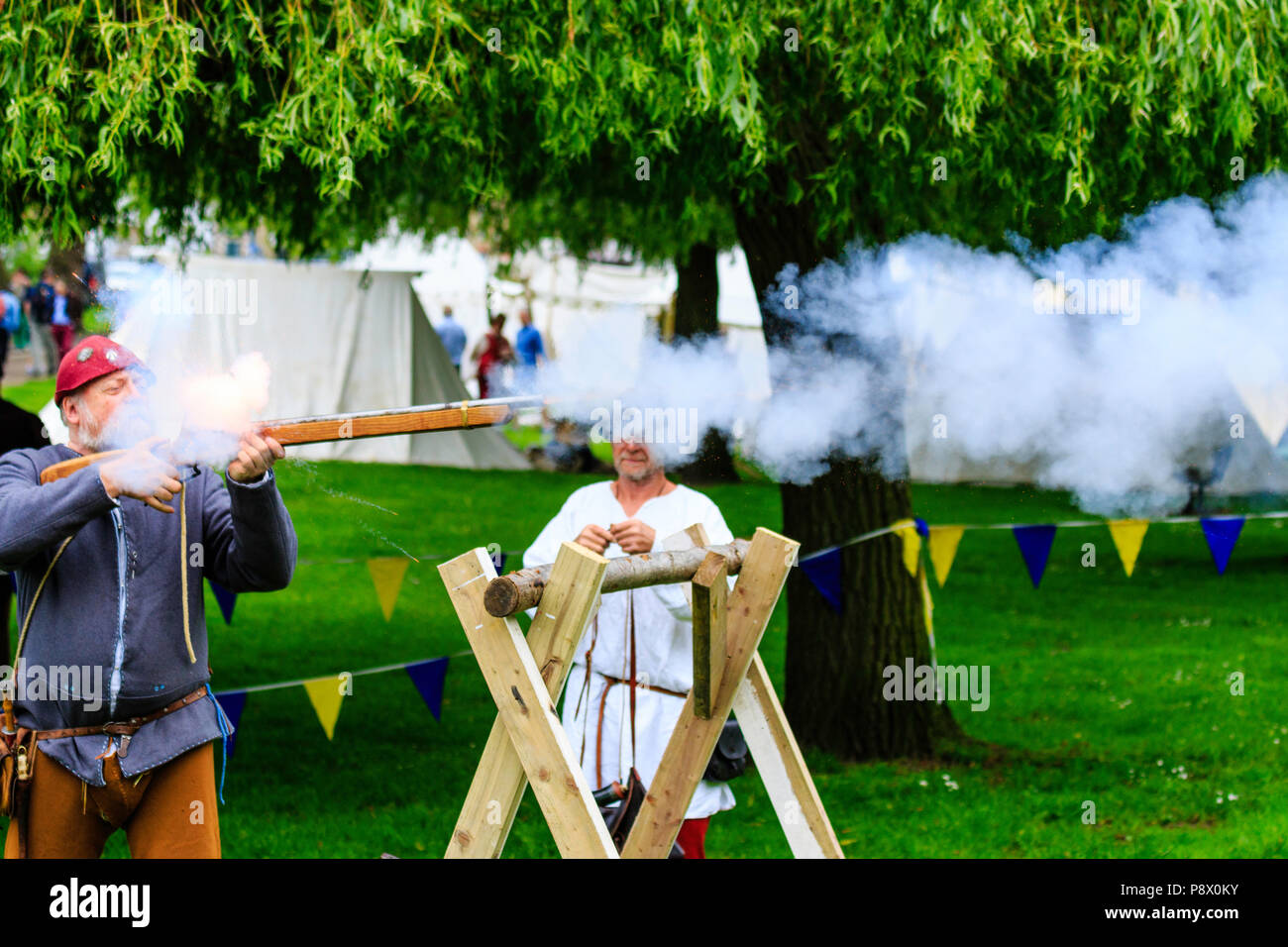 Man in medieval costume, firing harquebus, arquebus, early reconstructed gun, circa 16th century at living history re-enactment event - Stock Image