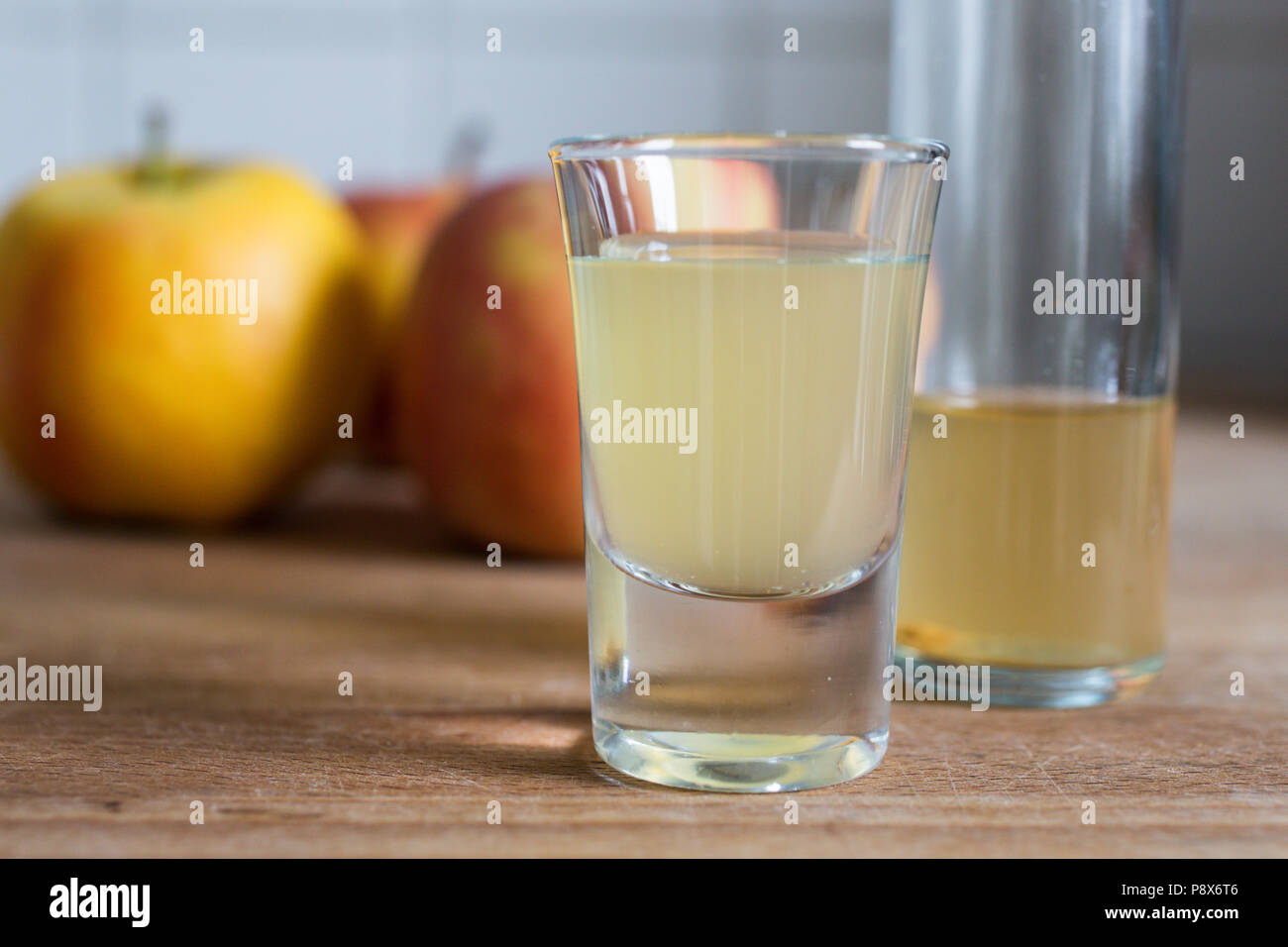 a glass of healthy cloudy fermented apple cider vinegar with apples