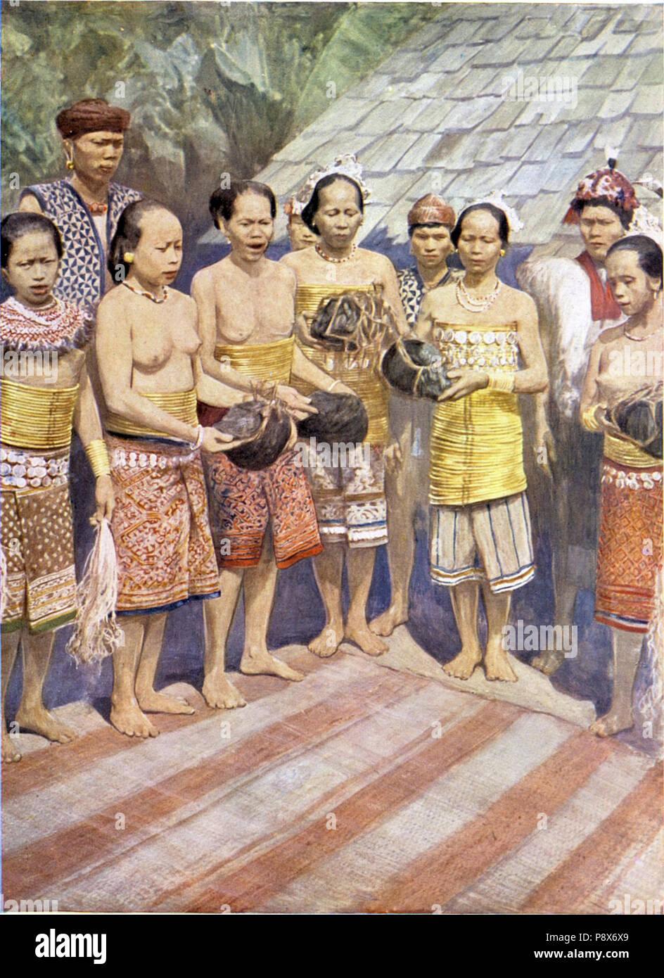 86 Dajakfrauen mit Menschenschädeln den Händen, zu einem Tanze versammelt - Stock Image