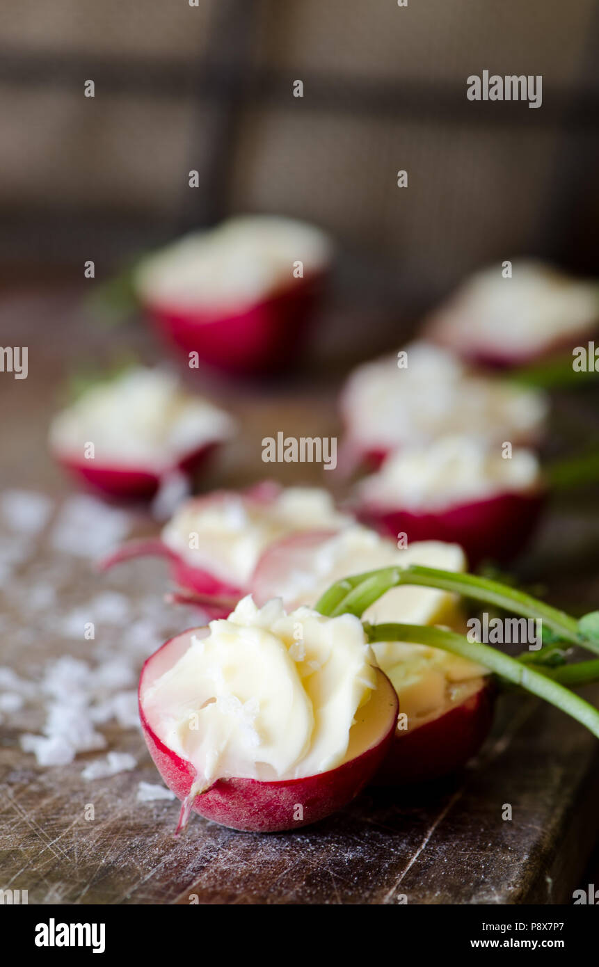 Radishes with unsalted butter and sea salt on the dark wooden background Stock Photo