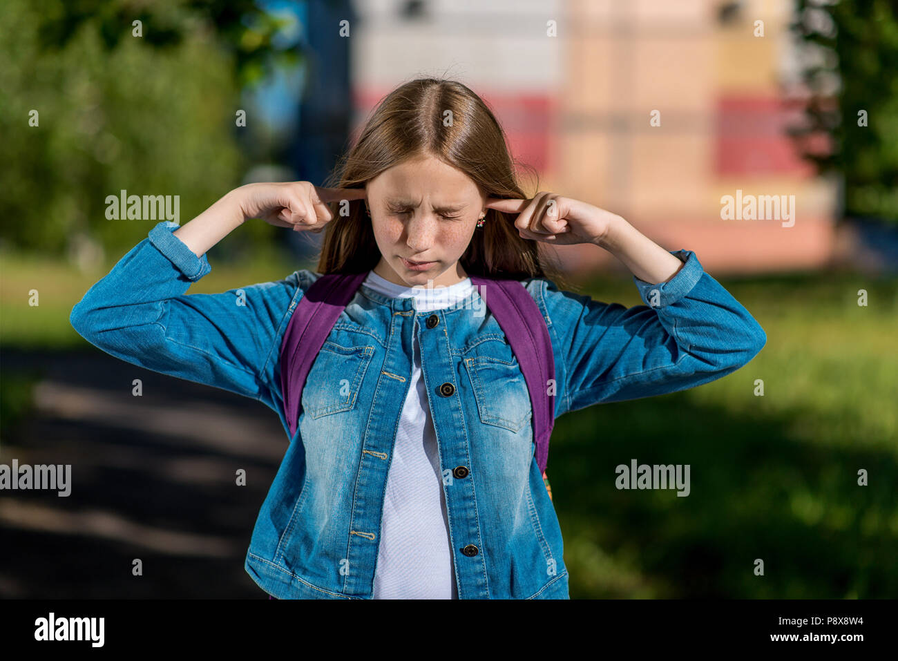Girl schoolgirl teenager. Summer in nature. Fingers cover ears. The concept does not hear anything, very loud, unbearable, noisy. Emotions is naughty playing the fool. - Stock Image