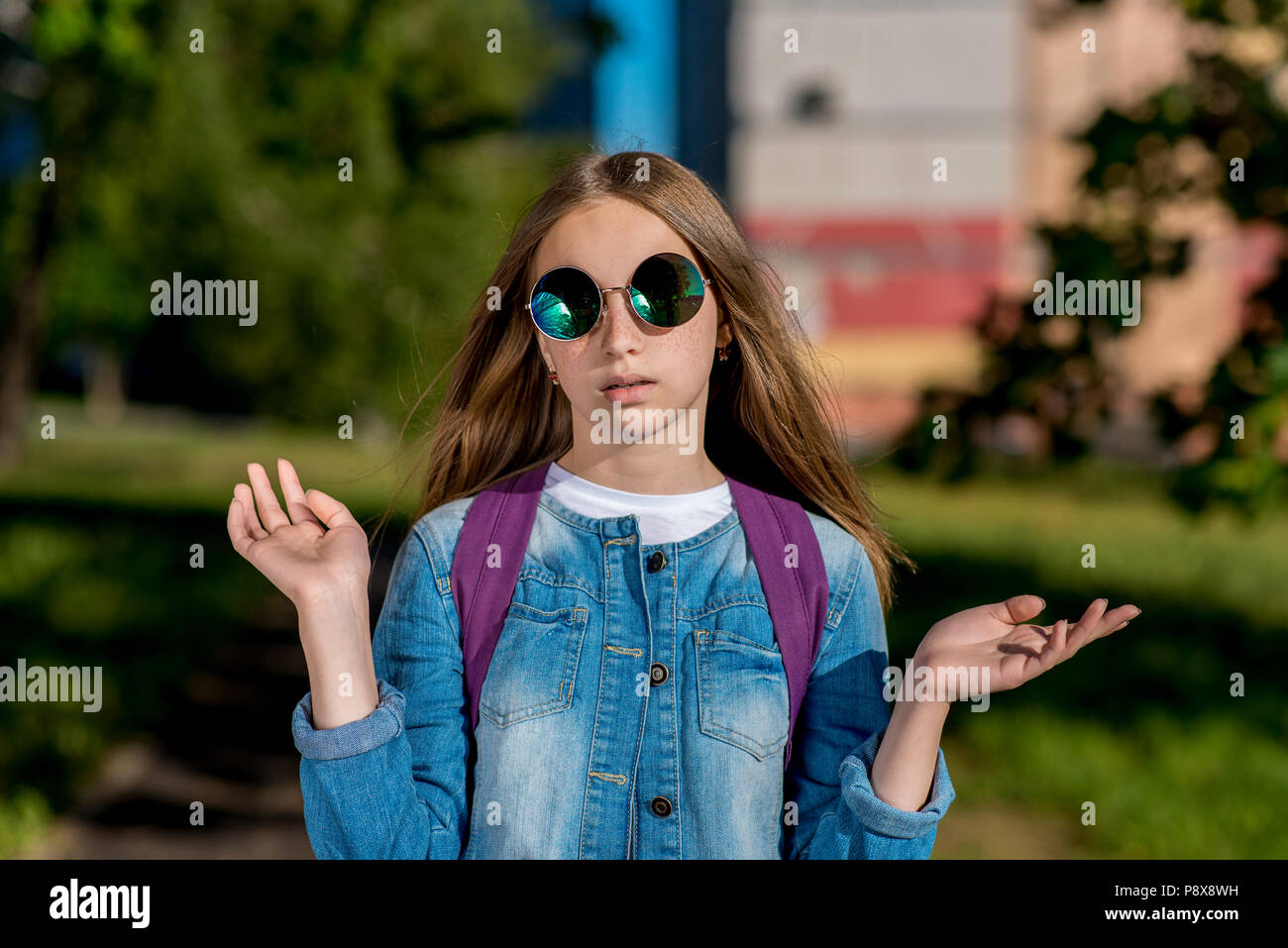 Teenage girl in summer outdoors. In jeans clothes and sunglasses. He raises his hands to sides. The concept of indignation is what I could do. Emotion is a wonder of frustration and resentment. - Stock Image