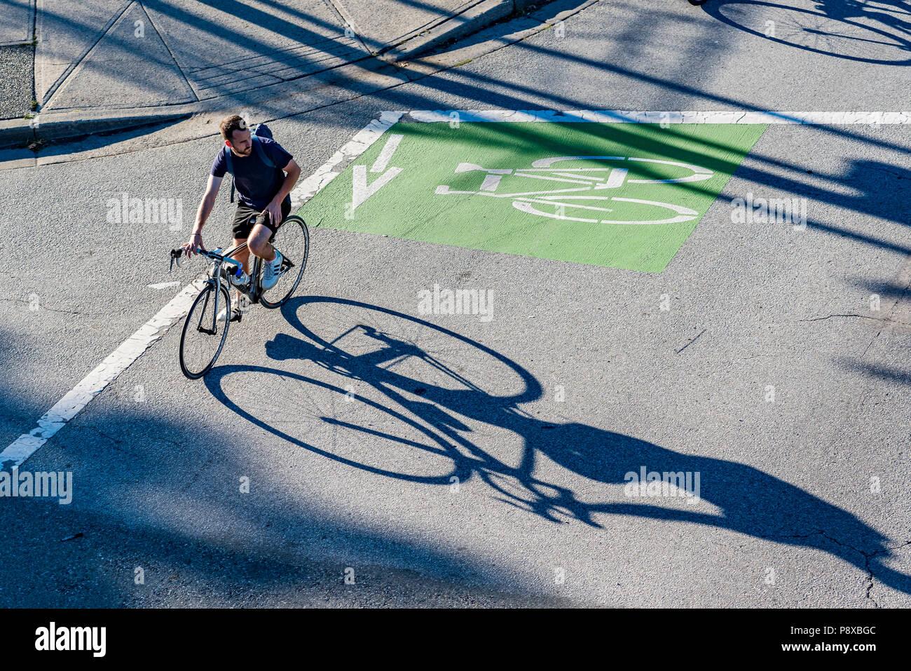 Cyclist using dedicated bike lane, Vancouver, British Columbia, Canada. Stock Photo