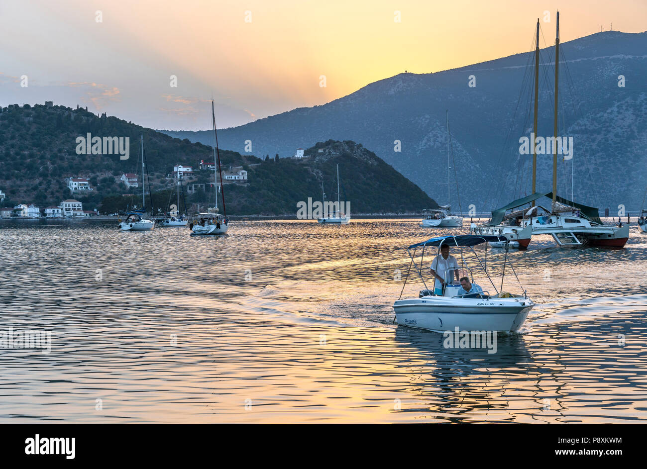 Yachts moored in Vathy harbour at sunset. On the island of Ithaca, Ionian Sea, Greece - Stock Image