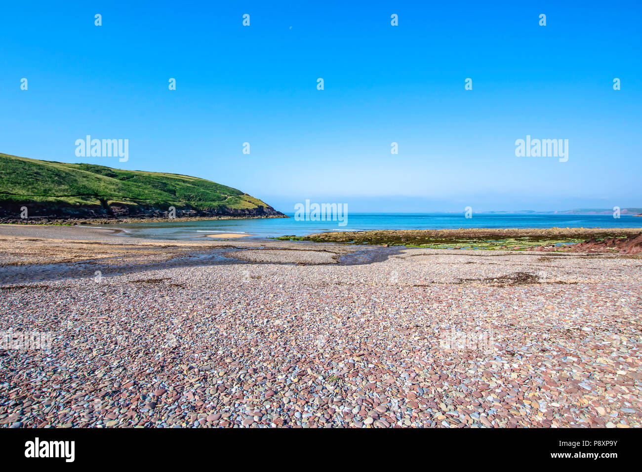 Beautiful scenery of dramatic Pembrokeshire coastline,South Wales, Uk in summer.Scenic landscape of british coast.Pebbles on shore of calm bay. Stock Photo