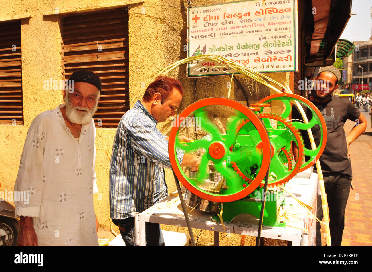 Ahmedabad: Two mens are reparing a sweet sugar cane dring - Stock Image