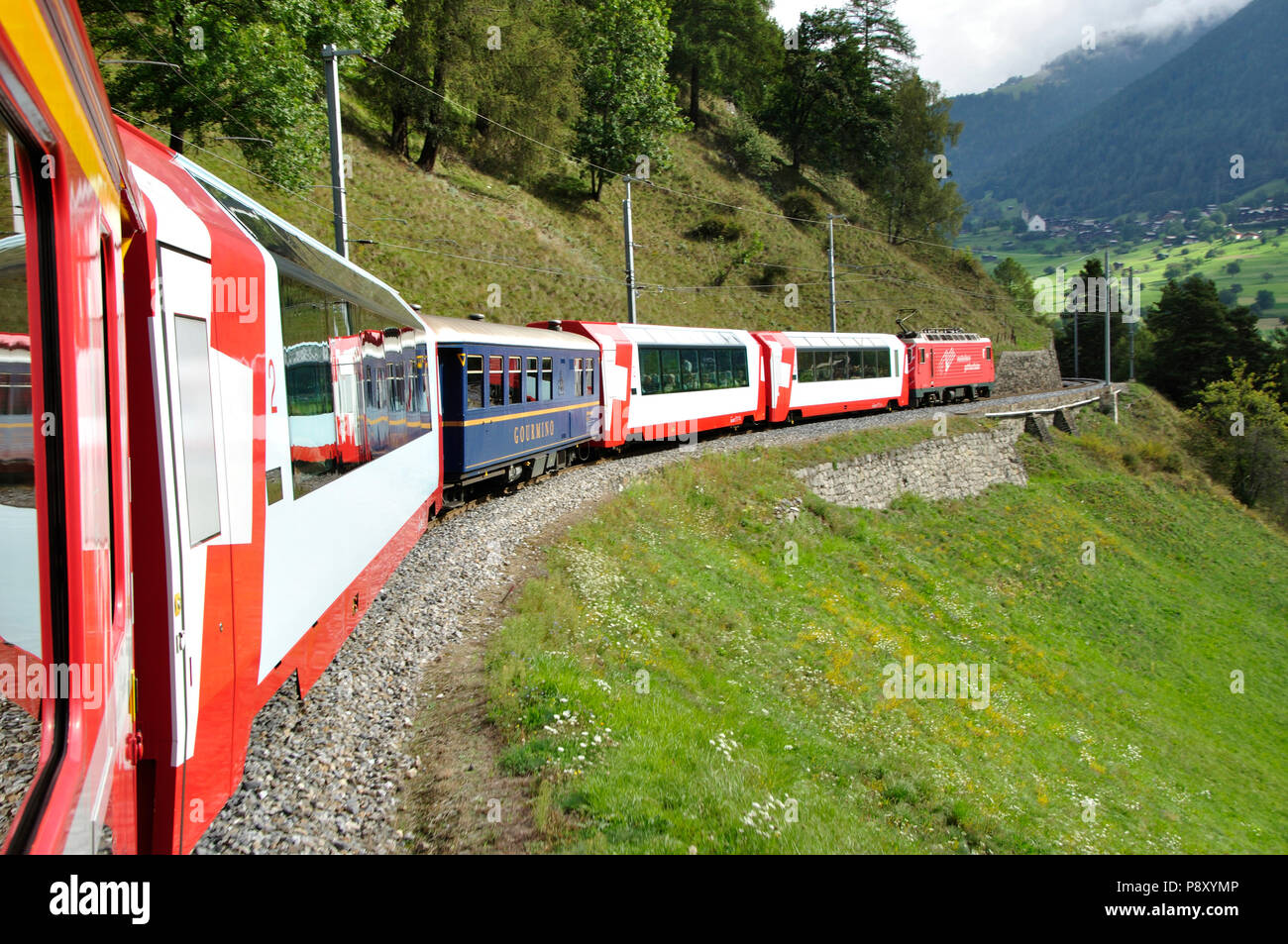 The glacier Express train is driving across the swiss alps and through the Unesco World heritage from Zermatt to St. Moritz - Stock Image