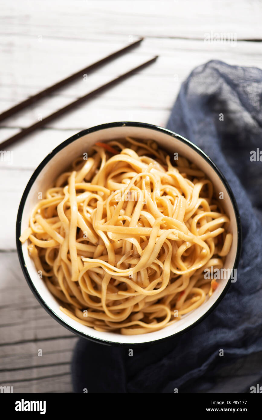 high angle view of a white ceramic bowl with yakisoba noodles, with vegetables and yakisoba sauce, on a white rustic wooden table next to a pair of ch - Stock Image