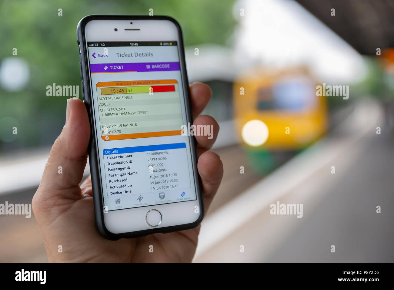 BIRMINGHAM, UK - 19 JUNE, 2018 : Close-up of an iPhone 6 displaying an electronic train ticket, with a train at the station platform behind. - Stock Image