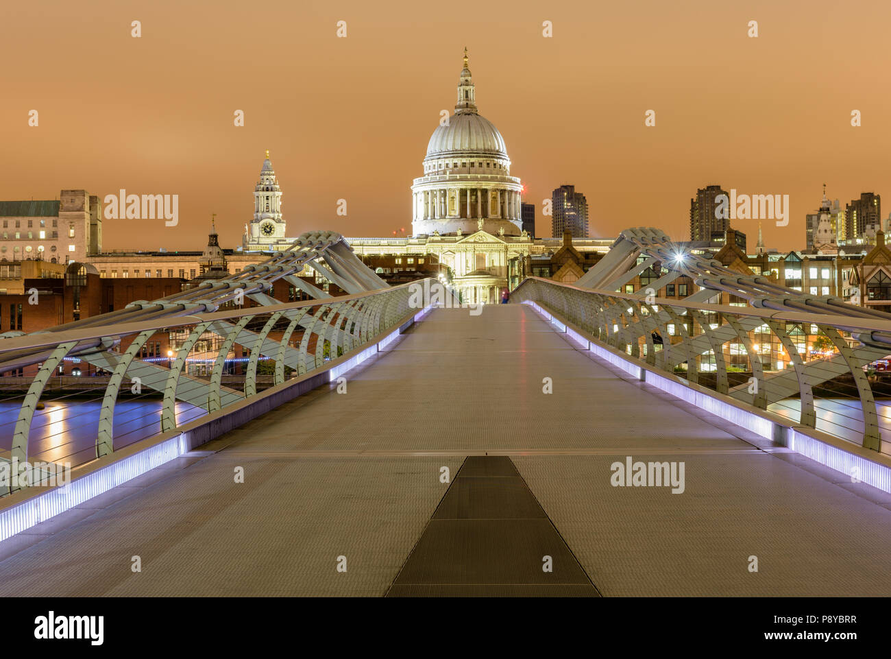 Head on landscape view of St Pauls Cathedral at night from a central position on the London Millennium Footbridge - Stock Image