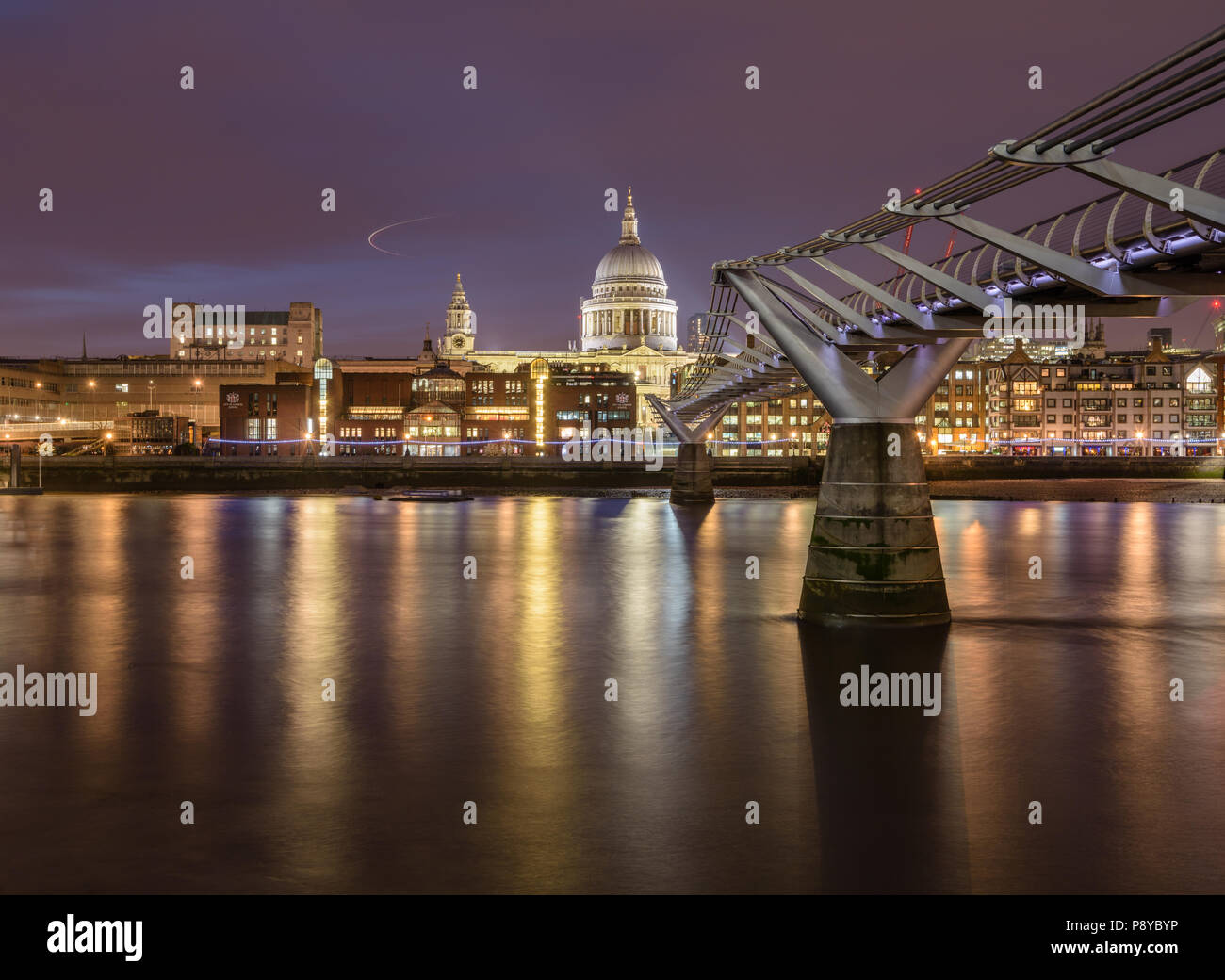 Long exposure landscape view of St Pauls Cathedral and the London Millennium Footbridge at night with lights reflected in the River Thames - Stock Image