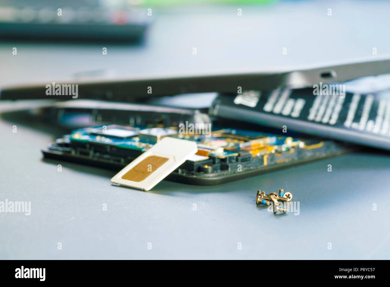 Disassembled mobile phone in the service centre with internal components of the camera and speaker. - Stock Image