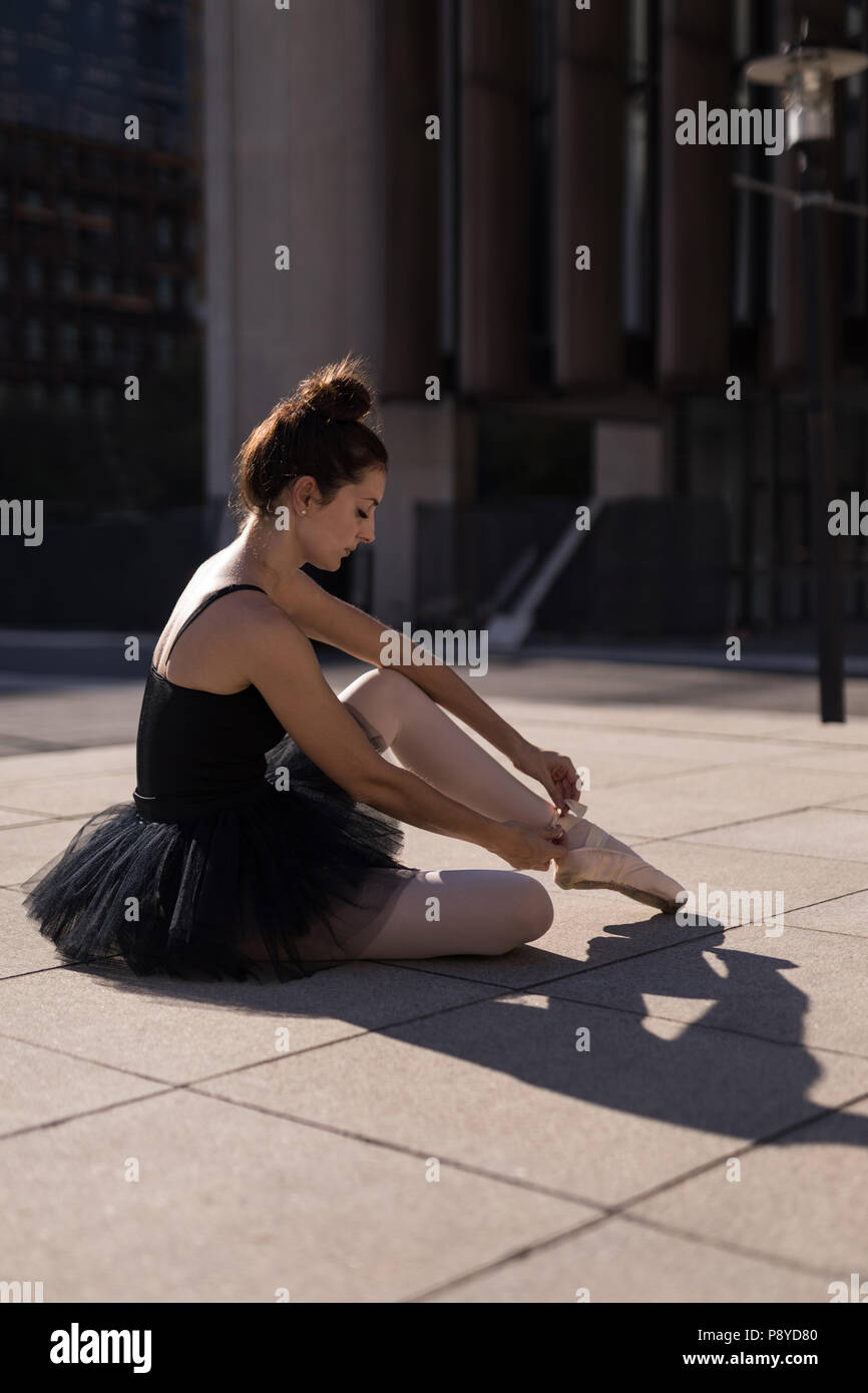 Female ballet dancer tying the ribbon on her ballet shoes - Stock Image