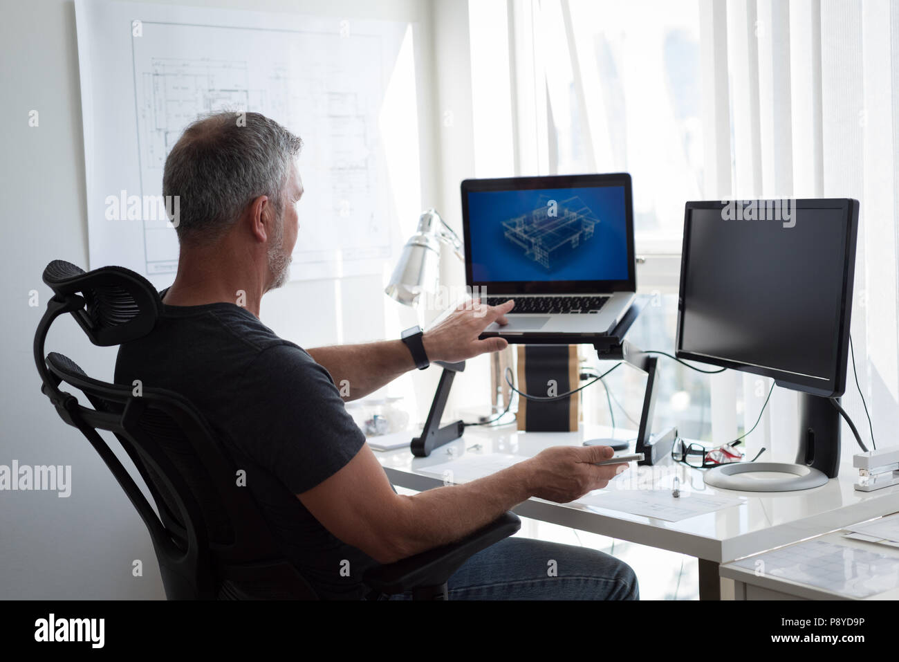 Man preparing architectural design on laptop and computer - Stock Image