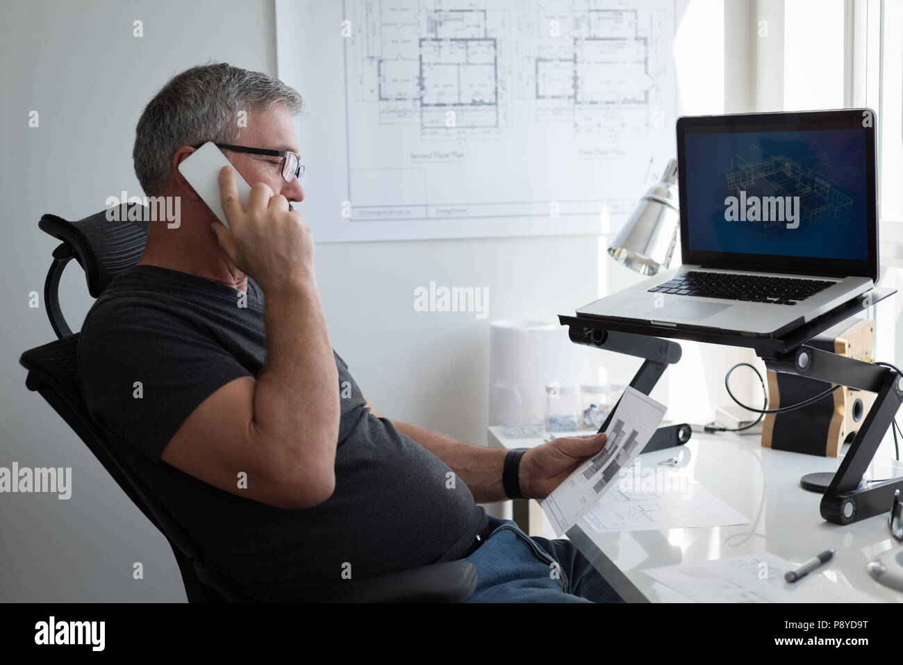 Man talking on mobile phone at home - Stock Image