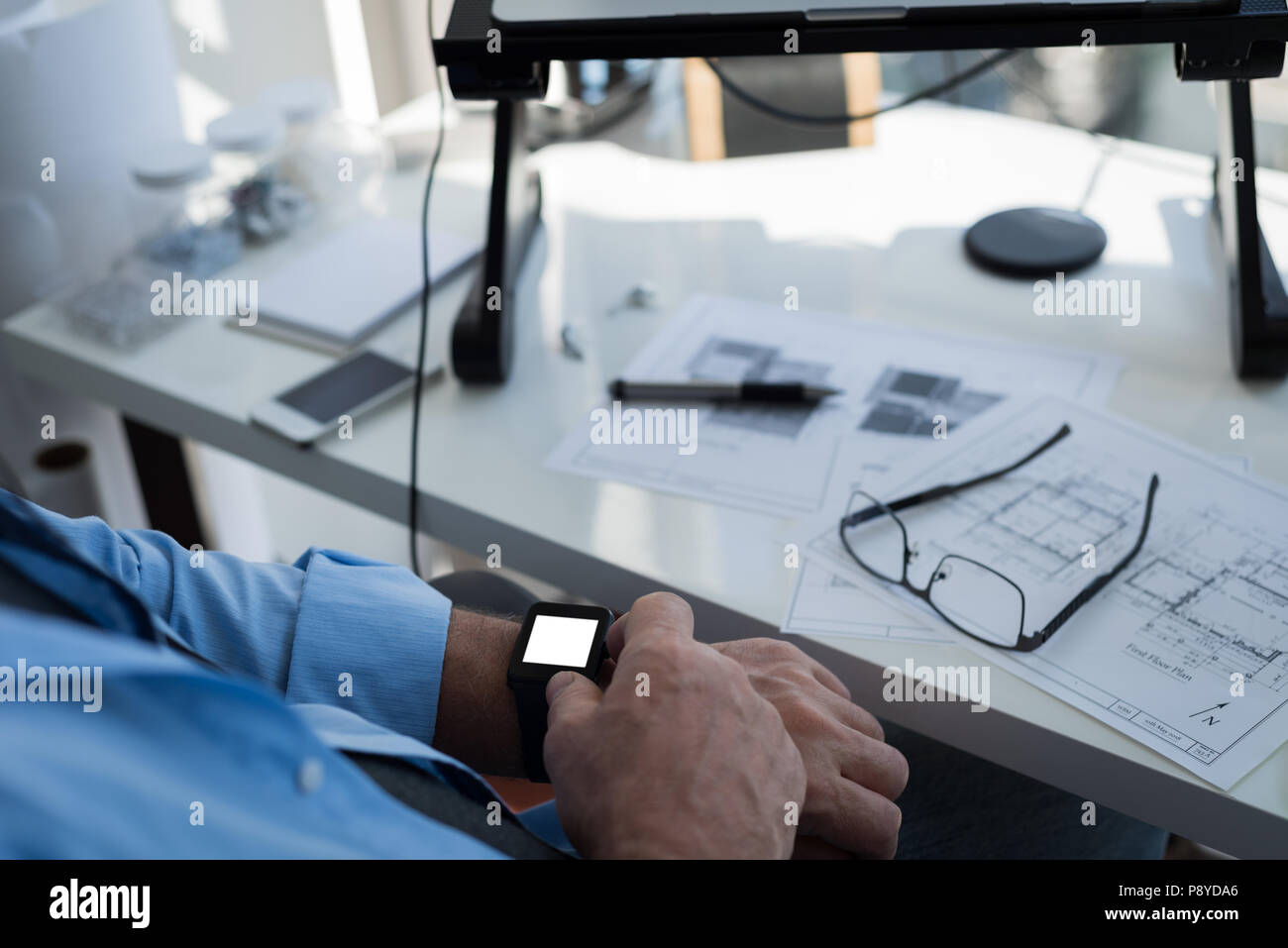 Man using smartwatch at home - Stock Image
