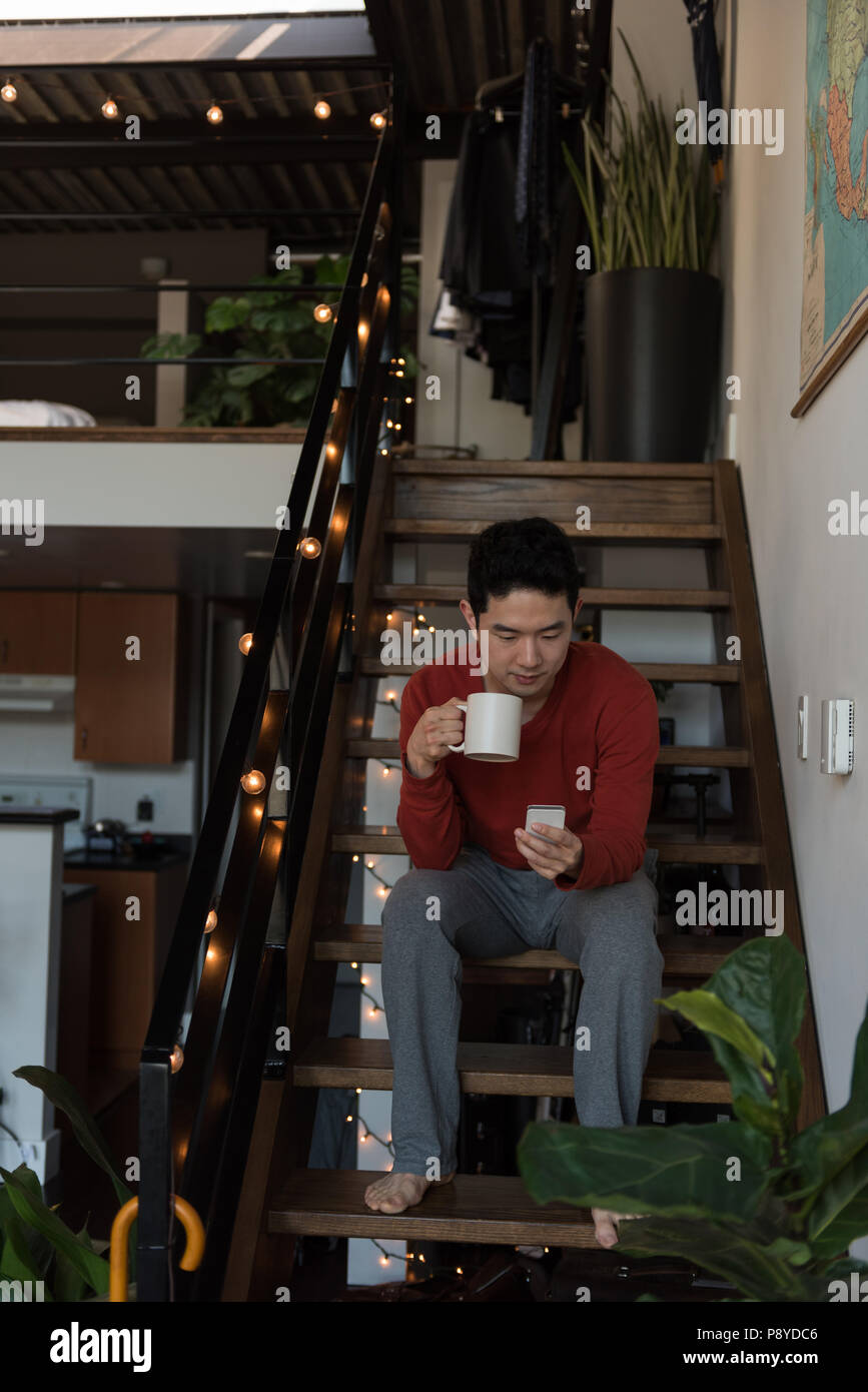 Man having coffee while using mobile phone on stairs - Stock Image