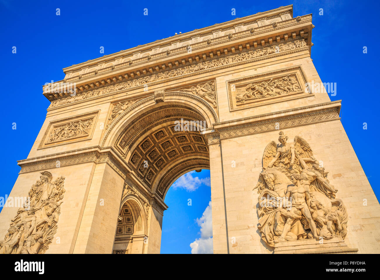 Bottom view of Arch of Triumph at center of Place Charles de Gaulle in a beautiful sunny day with blue sky. Popular landmark and famous tourist attraction in Paris capital of France in Europe. - Stock Image