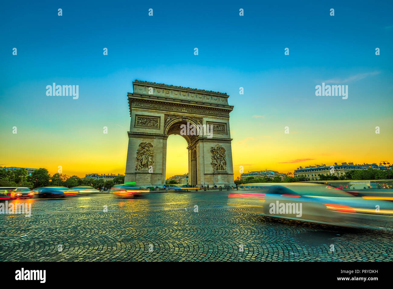 Arch of triumph. Arc de Triomphe at the western end of the Champs Elysees at the center of Place Charles de Gaulle in Paris at sunset with car traffic. Paris capital of France in Europe. - Stock Image