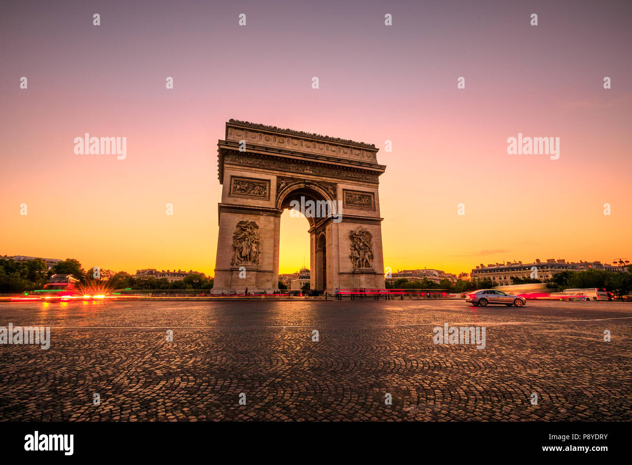 Arch of triumph at twilight. Arc de Triomphe at end of Champs Elysees in Place Charles de Gaulle with cars and trails of lights. Popular landmark and tourist attraction in Paris capital of France. Stock Photo
