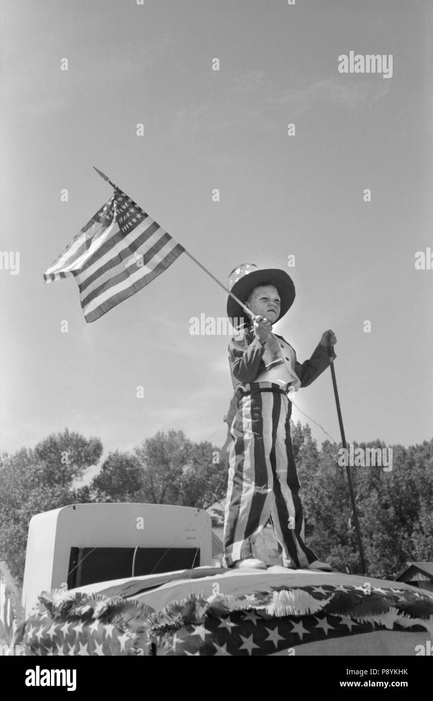 Young Boy in Patriotic Costume Waving American Flag during Fourth of July  Parade 13f96d4e5e1f